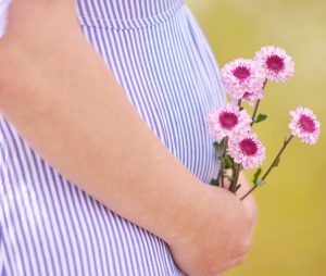 woman with baby bump holding flowers